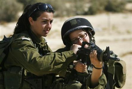 File picture shows Israeli platoon commander Racheli Levantal of the Karakal ground Battalion checking a soldier's weapon during a training session at a military base in southern Israel,