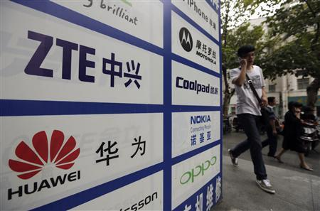 Man walks past an advertisement board showing the logos of Huawei and ZTE on it, outside a mobile phone repair shop in Wuhan