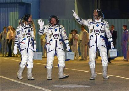 The International Space Station crew members U.S. astronaut Nyberg, Russian cosmonaut Yurchikhin and Italian astronaut Parmitano walk after donning space suits before the launch at the Baikonur cosmodrome